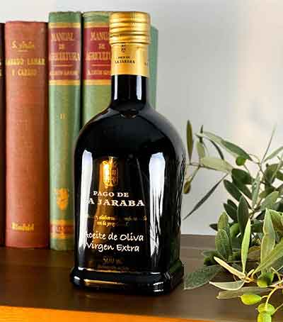Aceite-de-oliva-virgen-extra-la-jaraba-en-estanteria-con-libros-y-rama-de-oliva