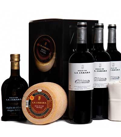 Estuche compuesto por tres botellas de vino tinto Pago de La Jaraba, botella de aceite y queso manchego artesano